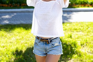 Beautiful young brunette girl, fashion style urban life. Student in park bright summer day outdoors.