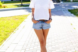 Beautiful young brunette girl in short denim shorts with glasses, fashion style urban life. Student in park bright summer day outdoors. Resting after study. Posing on a street in the city.