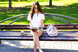 Beautiful girl student with glasses and a bag of coffee, sitting on  park bench, reading  book, fashion style, school life, in the summer   sunny day in the fresh air. Schoolgirl resting.