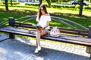 Beautiful girl student with glasses and a bag of coffee, sitting on  park bench, reading  book, fashion style, school life, in the summer   sunny day in the fresh air. Woman relaxing.