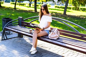 Beautiful girl student with glasses and a bag of coffee, sitting on  park bench, reading  book, fashion style, school life, in the summer   sunny day in the fresh air.