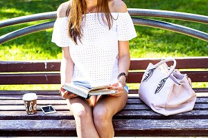 Young beautiful woman sitting in the park summer spring day, reading a book, with coffee, tea, phone bags, white sneakers, shorts and   blouse, is enjoying rest slim tanned girl.