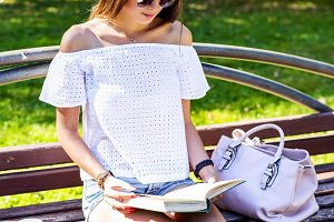 Student brunette girl sitting on a park bench   street in the city summer day reading  book, with the phone, coffee mug bag, in short shorts white t-shirt, enjoy your vacation, fashion lifestyle.