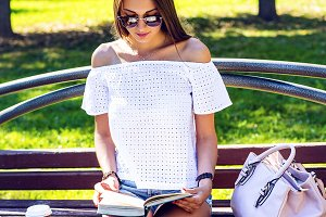 Young beautiful brunette student in glasses sits on a bench in the park summer day, reading  book, coffee, tea, mobile phone bag, tanned relaxing after lessons at the institute in the fresh air.