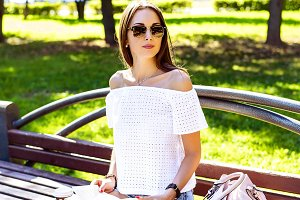 Beautiful brunette girl with glasses sitting on a park bench   book and  bag resting reading, after school. Fashion style, lifestyle female students.