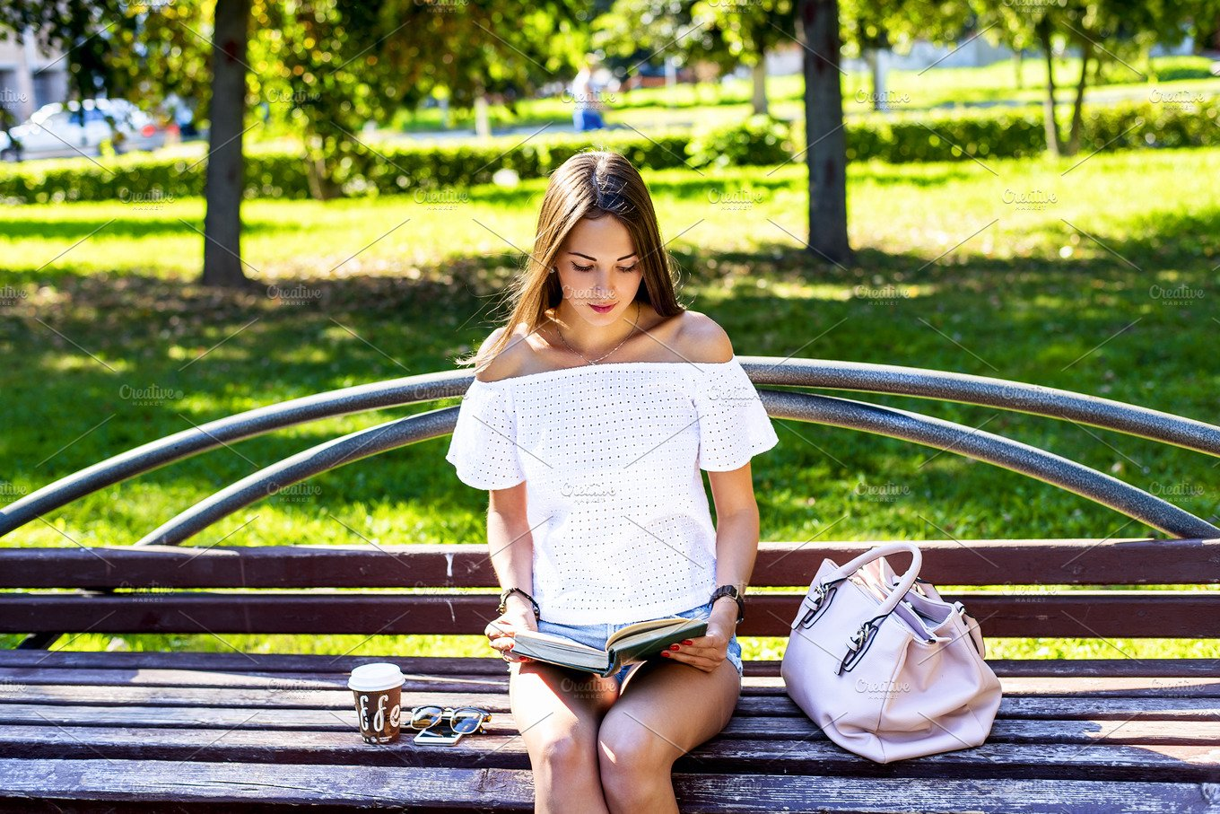 Young Girl Student Sitting On A Park Bench Reading Paper Book With