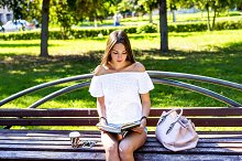 Young girl student sitting on a park bench, reading  paper book with  cup of coffee or  tea bag in  white jacket,  bright summer day outdoors, fashion lifestyle.