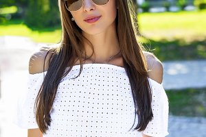 Beautiful young girl student brunette in glasses, fashion style glamorous woman in a park in the summer outdoors. Close-up, people concept, portrait of  stylish, business  in the city.