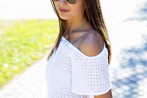 Beautiful young girl student brunette in glasses fashion style glamorous woman in a park in the summer outdoors. Close-up, concept, business  in the city. In jeans and  white T-shirt