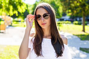 Beautiful brunette fashion style, wearing glasses and a white blouse, model, glamor business woman outdoors in the park in the open air, in city lifestyle. Girl student.
