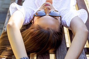 Beautiful brunette student girl lying on a park bench relaxing in the fresh air. Close-up. Fashion style glamorous woman, summer day in the city during the     sleeping, sunbathing.