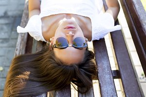Beautiful brunette student girl lying on a park bench relaxing in the fresh air. Close-up. Fashion style glamorous woman, concept idea long hair look  the  asleep sunbathing.