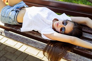 Beautiful brunette student girl lying on a park bench relaxing in the fresh air. Close-up. Fashion style glamorous woman, concept idea long hair look  the  stretches.