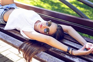 Young modern student beautiful girl, brunette lying on a park bench relaxing in the fresh air. Close-up. Fashion style glamorous woman, concept idea long hair look  the  stretches.
