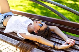 Young modern student beautiful girl, brunette lying on a park bench relaxing in fresh air. Close-up. Happy woman.