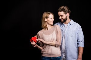 Couple holding heart shaped gift