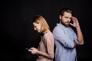 Woman using smartphone with man