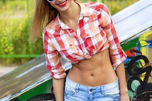 Haired beautiful girl with glasses, smiling outdoor young happy, in a shirt,  bright sun in denim shorts, fashion style glamorous life, posing enjoying summer day