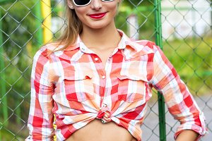 Beautiful girl in glasses, shirt, jeans, young happy smiling bright sunny summer day, fashion style, lifestyle, enjoying summer tanned sexy
