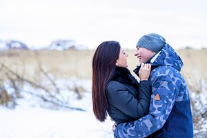 A man and a woman in a park in winter outdoor fun, enjoying holiday. Young beautiful pair of newlyweds pleased Happy winter day. Fashion lifestyle. A happy family.
