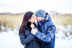 Beautiful young couple hugging in a park in winter snow-covered field, a gentle hug, fashion lifestyle, enjoying love and feelings on a date and first kiss, outdoors.
