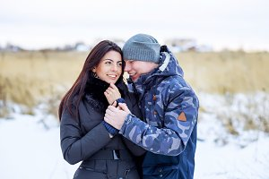 Beautiful young couple hugging in a park in winter snow-covered field, a gentle hug, fashion lifestyle, enjoying love and feelings on a date smiling dream of a happy family outdoors.