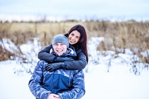 Happy young couple lovers man and woman having fun in winter park on a snowy meadow, smiling happy, date newlywed, love couple. Fashion style of life, rest in nature.