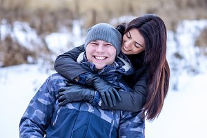 Beautiful couple relaxing, having fun in the park in the winter outdoors, playing hug. Smiling happy enjoying love, bright sunny winter day. Fashion lifestyle. Happy family carefree winter jackets.