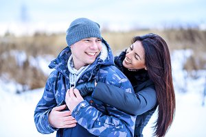 Happy young couple playing on nature bright sunny winter day, fashion lifestyle cheerful smile love each other, having fun in the park in the snow in a cap and winter jackets.