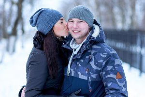 Girl kissing her boyfriend in the fresh winter air, on a street in a park in the snow in a cap and gloves, fashion style, the couple, smiling. A man and a woman love each other.