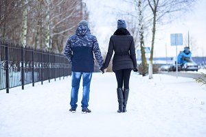 Couple holding each other's hands, the winter goes on the road, enjoying a stroll, a love couple. Fashion lifestyle. Husband and wife are going through the park holding hands in the winter.