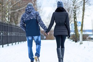 Couple holding each other's hands, the winter goes on the road, enjoying a stroll, a love couple. Husband and wife are going through the park holding hands in the winter. The movement of people.