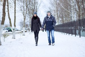 Young couple holding hands goes through the snowy park. Fashion style of life, happy love couple resting in the open air. In the winter jackets and caps.