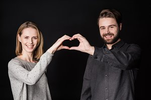 Couple performing heart symbol