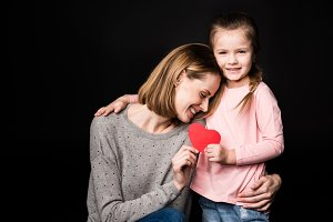 Mother and daughter with paper heart