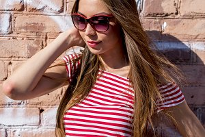 Close up lifestyle fashion portrait Beautiful girl smiling standing near brick wall in red fashion style shirt and white shorts glamorous bright summer sun happy