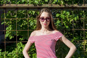 Beautiful girl in a bright red T-shirt, fashion lifestyle, posing against the backdrop of the fence with green leaves of bushes, resting, sunbathing on nature in sunglasses