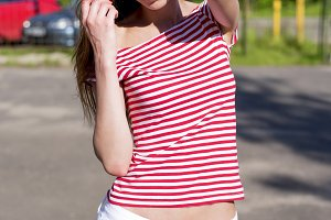 Beautiful young woman, outdoors, resting in a bright red T-shirt, fashion style, happy brunette hair straightening
