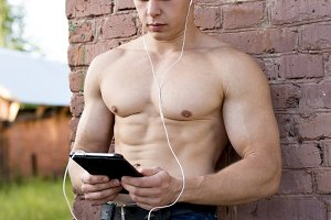 Young bodybuilder man is resting on the nature of the tablet in hands and watching a movie, listening to music, read e-books, in jeans at the brick wall