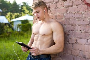 Young male athlete outdoors, resting against the wall, holding a tablet, listening to music, watching a movie, reading a book. A bright sunny day in nature, in jeans fashion style, urban life.