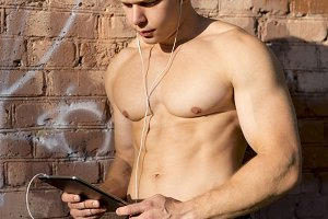 Bodybuilder man, standing at the wall watching a movie on the plate, listening to music, reading a message, in nature, in the city in the summer, the fashion lifestyle.