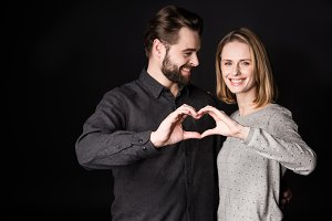 Young couple showing heart sign