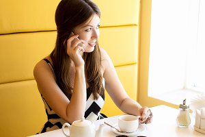 City life using the phone talking in a cafe. Young professional business woman sitting in a room in a cafe looking. Beautiful brunette girl. Lunch or breakfast bright summer day.