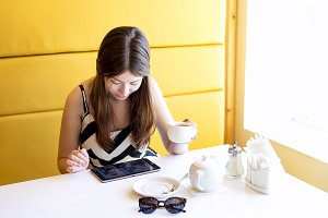 A beautiful young brunette woman indoors cafe. Eat breakfast or lunch with a cup of coffee or tea, looking at the tablet, photos sitting in social networks, puts huskies. Correspondence with friends.