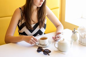 Young beautiful girl sits in a cafe, sunny day, holding the phone, reading a message, social networking, fashion style model woman in a dress with coffee or tea, breakfast or lunch.