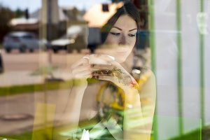 Young beautiful girl sits in a cafe, sunny day, holding a cup, fashion style, model woman with coffee or tea, breakfast or lunch, photos behind glass, dreaming, thinking pensive.