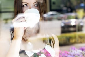 Beautiful brunette girl with the glass showcase in a cafe, sunny day, a mug of tea, coffee, plates, fashion style, breakfast, lunch, looking out the window, resting time, business woman enjoying