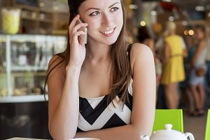 Beautiful young brunette woman, talking on the phone with a tablet, a mug of tea, coffee, fashion, city, breakfast restaurant, business woman discussion resting smiling