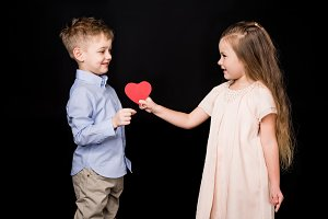 girl giving paper heart to boy