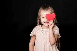 Little girl with red paper heart